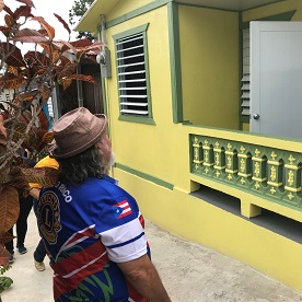 A Lion admires the work done to repair and repaint a home destroyed in Hurricane Maria.