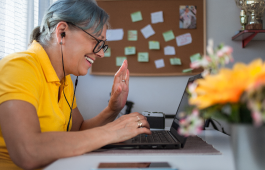 Uma mulher usando fones de ouvido sorri e acena para alguém em uma reunião virtual.