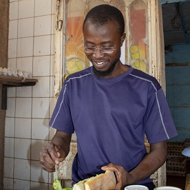 Idrissa regained his vision and was able to return to work at his café thanks to SightFirst. In this photo, he is making his specialty, an avocado sandwich.