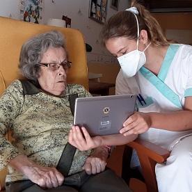 O funcionário de uma casa de repouso ajuda um residente a se conectar com sua família por meio de vídeo neste momento em que uma ordem de distanciamento social restringe as visitas.