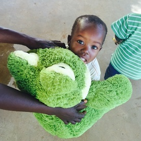 A toddler looks at the camera while holding a big, green plush toy frog.