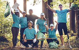 Um grupo de Leões comemorando durante um projeto de serviço na floresta.