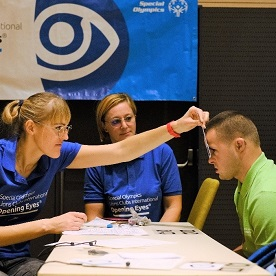 Volunteers at a Special Olympics Lions Clubs International Foundation Opening Eye event test the vision of a Special Olympics athlete.