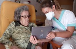 Um profissional da saúde usando máscara olha para um tablet com um paciente.