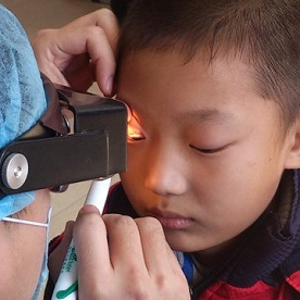 A young boy has his eyes examined thanks to the SightFirst China Action program.