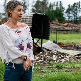 A woman looks over her property after bushfires destroyed her home. With funding from LCIF, Lions are helping to rebuild the community.