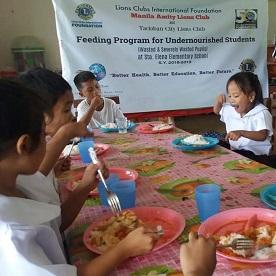 As crianças se reúnem em volta da mesa de jantar, enchendo suas barrigas com uma refeição nutritiva.
