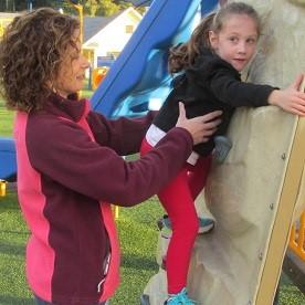 Natalie recebe ajuda da sua mãe para escalar a parede.