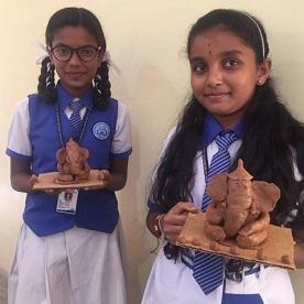 Dois alunos do Lions Quest da Índia, mostram com orgulho seus ídolos Ganesha feitos com materiais ecológicos.