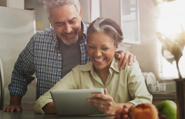 Smiling couple looks at tablet