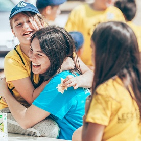 A young girl hugs a Leo at a weekend camp for underserved children in Portugal.